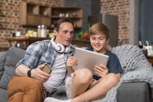 happy smiling father and son sitting on couch use FKPY7SN 300x200 - Happy Smiling Father And Son Sitting On Couch Use Tablet Computer, Parent Spending Time Child
