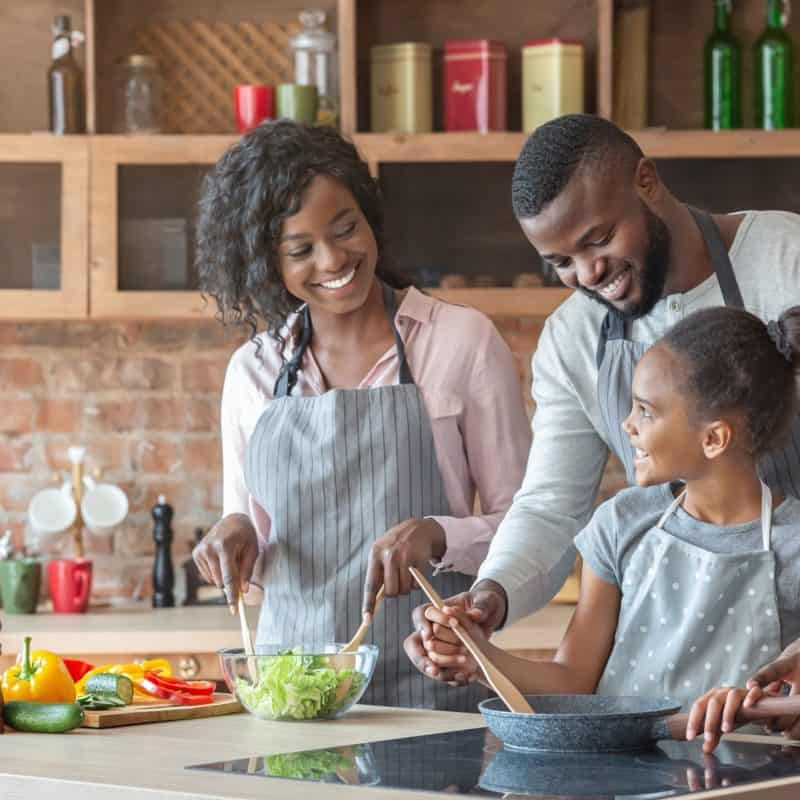 young parents teaching daughter how to cook QTLZGW8 800x800 - 7 Cool Things To Do With Your Kids At Home